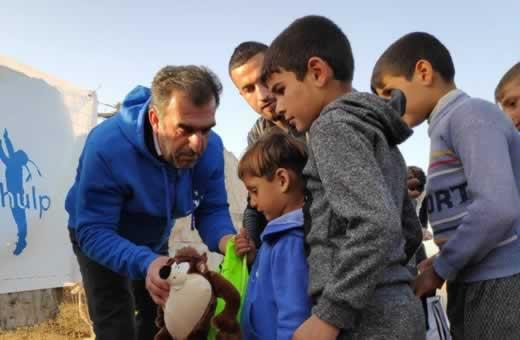 vrijwilliger deelt speelgoed uit in vluchtelingenkamp
